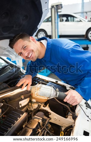 Mechanic examining under hood of car with torch at the repair garage - stock photo