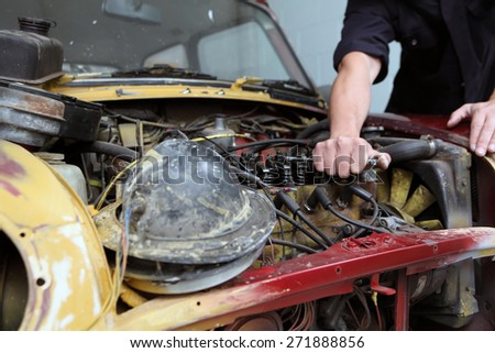 Mechanic fixing a car - stock photo