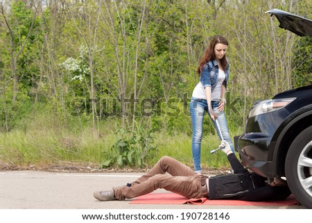 Mechanic fixing a car on a roadside breakdown working under the engine compartment as the female driver helps him by handing him a socket spanner - stock photo