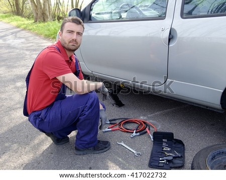 mechanic fixing a car problem on the road - stock photo