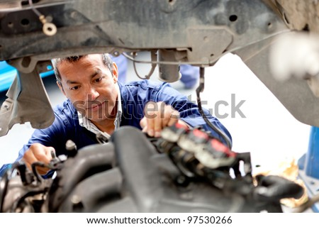 Mechanic fixing an engine of a car at the garage - stock photo