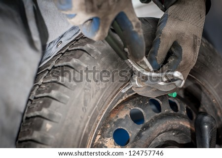 Mechanic fixing car tire - stock photo