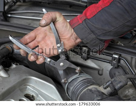 Mechanic  fixing hose clamp with pliers tool  at car engine - stock photo