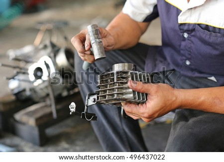 mechanic fixing motocycle engine