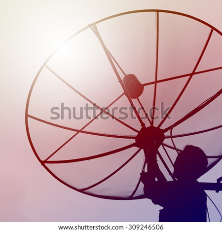 Mechanic fixing Satellite dish with vintage filter style - stock photo