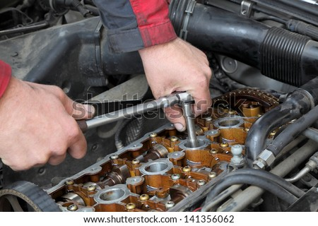Mechanic fixing spark plug to open car engine with ratchet, visible camshafts,  pulley, belt, timing chain - stock photo