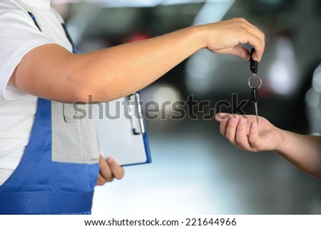Mechanic giving car key while shaking hand to a client in a garage - stock photo