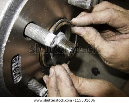 mechanic hands fixing car brakes and rotors rubber gasket - stock photo