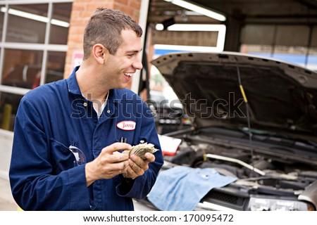 Mechanic: Happy to get money for repair work. - stock photo