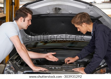 Mechanic Helping Apprentice To Fix Engine - stock photo