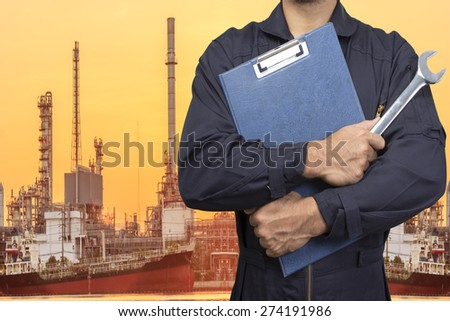 mechanic holding a clipboard of service order with wrench for working at petrochemical oil refinery in sunrise - stock photo