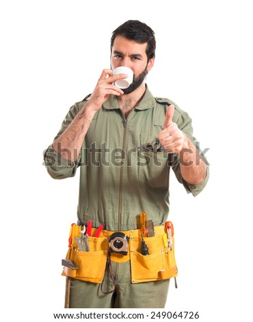 mechanic holding a cup of coffee  - stock photo