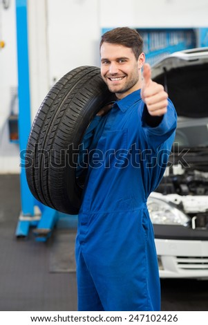 Mechanic holding a tire wheel at the repair garage - stock photo