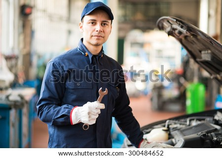 Mechanic holding a wrench in his garage - stock photo