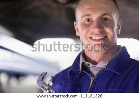Mechanic holding an adjustable pliers while looking at camera in a garage