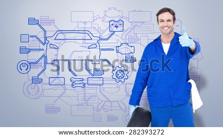 Mechanic holding tire while showing thumbs up against grey vignette - stock photo