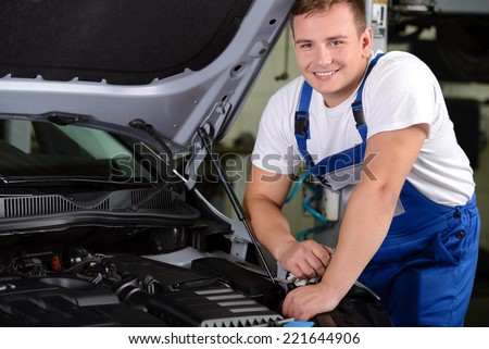 Mechanic in auto repair shop standing next to car with open hood - stock photo
