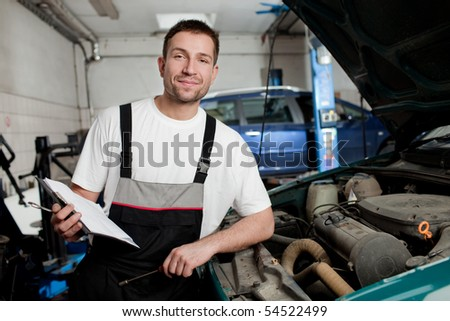 Mechanic in auto repair shop standing next to car with open hood