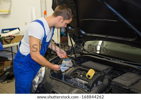 Mechanic in garage or workshop checking motor oil level at a car