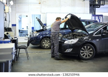 Mechanic in overalls opened hood of black car in small service station. - stock photo