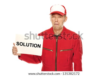 "Mechanic in red Overall wth whining face expression and ""Solution"" sign. Who needs a solution? I�´d like to keep my problem."