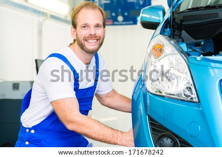 Mechanic in workshop or MOT with car or auto for service inspection - stock photo