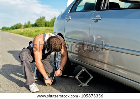Mechanic lifting a car with jack-screw - stock photo