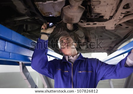 Mechanic looking the below of a car while holding a flashlight in a garage - stock photo