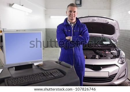 Mechanic next to a car and a computer in a garage - stock photo