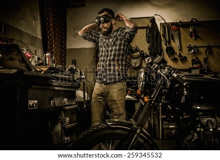 Mechanic preparing ford lathe works in motorcycle customs garage  - stock photo