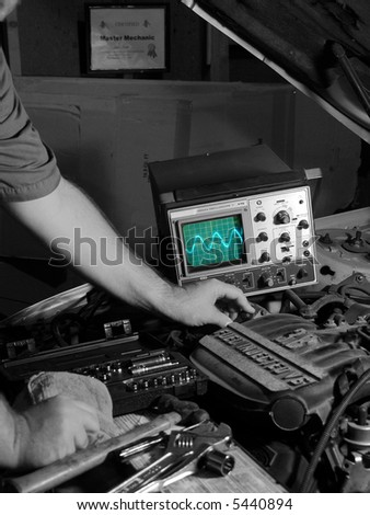 Mechanic probes engine with high tech oscilloscope - stock photo