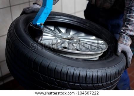 Mechanic removes  car tire closeup - stock photo