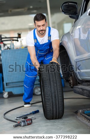 mechanic repair and  pushing a black tyre in workshop - stock photo