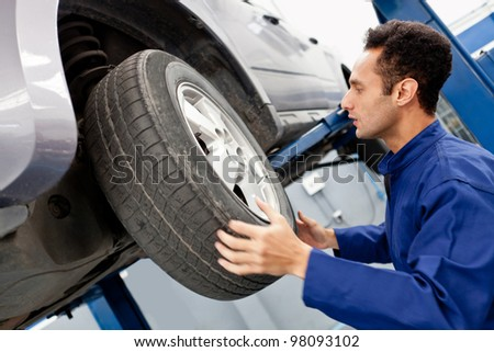 Mechanic repairing a car wheel at the garage - stock photo
