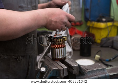 Mechanic repairing electric generator, repair of starter   - stock photo