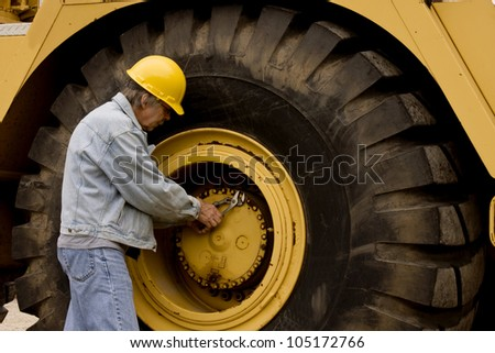 mechanic repairing huge truck tire on heavy equipment - stock photo