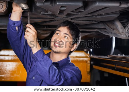 Mechanic Repairing Underneath Lifted Car - stock photo