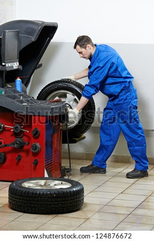 mechanic repairman balancing automobile car wheel on balancer - stock photo