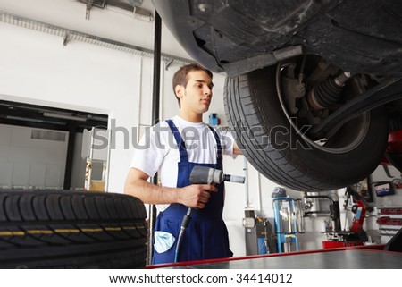 mechanic replacing car tyre in auto repair shop. Low angle view - stock photo