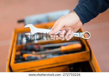 Mechanic's hand holding a wrench - stock photo
