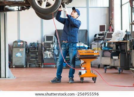 Mechanic screwing a tyre with a pneumatic wrench - stock photo