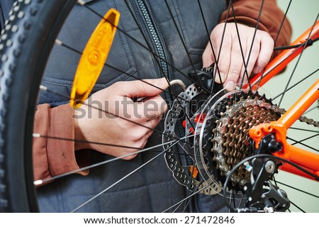 Mechanic serviceman repairman installing assembling or adjusting bicycle gear on wheel in workshop - stock photo