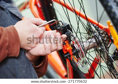 Mechanic serviceman repairman installing assembling or adjusting bicycle gear on wheel in workshop - stock photo
