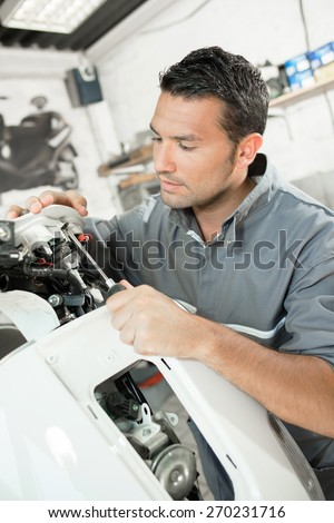 Mechanic servicing a scooter