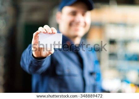 Mechanic showing a blank card - stock photo