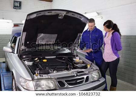 Mechanic showing a clipboard to a woman in a garage - stock photo