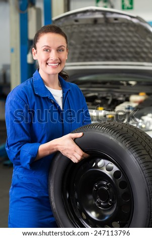 Mechanic smiling at the camera holding tire at the repair garage