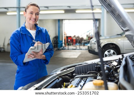 Mechanic smiling at the camera writing on clipboard at the repair garage - stock photo