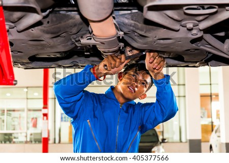 Mechanic standing and fixing under a lifted car with copy space - stock photo