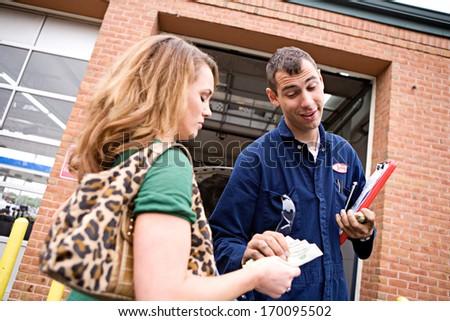 Mechanic: Taking customer's money for payment. - stock photo